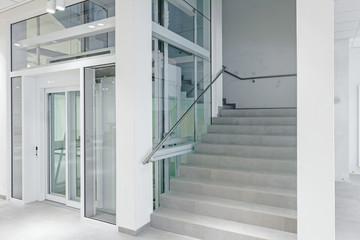 Front view of glass elevator in modern building.