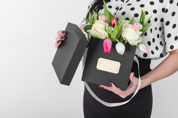 woman holding bouquet of roses and tulips in box