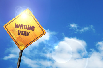 Yellow road sign with a blue sky and white clouds: wrong way