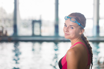 Female swimmer in an indoor swimming pool - looking at the camer