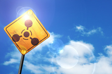 Yellow road sign with a blue sky and white clouds: Chemical weap