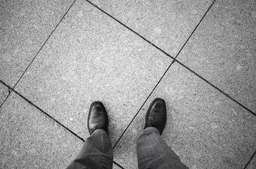Feet of an urbanite man in black new shining shoes