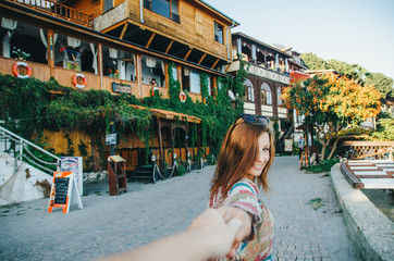 Girl leads to walk along the street with ancient wooden buildings in the Old town of Nessebar