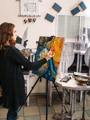 Hipster artist paints a colorful abstract painting. Closeup of painting process in art workshop. Creative hipster woman painter paints in her studio abstract colorful picture.