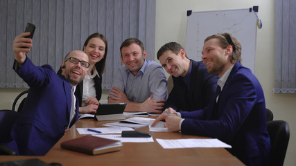 Business people making face while taking selfie in office