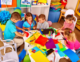 Group kids holding colored paper on table in kindergarten. Children use a colored origami paper.