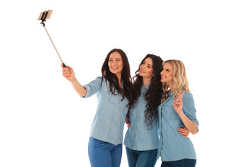3 casual young women taking a selfie with their phone
