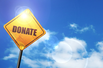 Yellow road sign with a blue sky and white clouds: donate