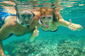 Underwater photo of a couple snorkeling at tropical ocean.