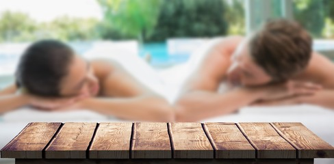 Composite image of couple lying on massage table at spa center