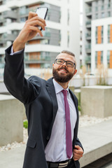 Young happy bearded businessman standing outside office building