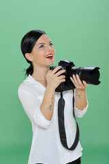 Portrait of a happy young woman holding a digital SLR camera. Vertical shot. Isolated on chroma green background