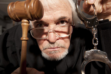 Old male judge in a courtroom striking the gavel