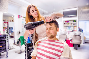 Professional hairdresser drying hair to her handsome client.