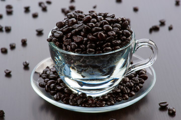 transparent glass cup filled with coffee beans on dark wooden