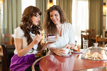Two women chatting,smiling and having snack in coffee, enjoying a dessert, at the coffee / cake shop