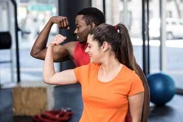Smiling woman and man contracting biceps