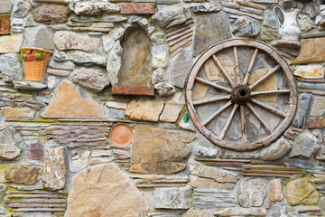 Background. A stone wall with a wooden wheel and a jug