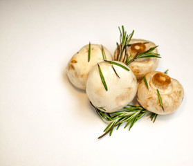 Fresh champignon mushrooms with spicy herbs on a light background