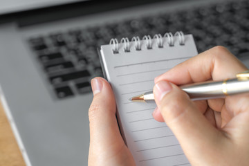 Woman  hand using a pencil noting over laptop