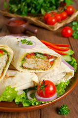 Fresh tortilla wraps with kebab and fresh vegetables on plate