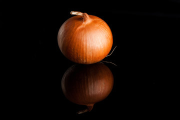 Whole unpeeled gold onion on black background with reflection