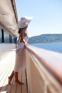 femme en maillot et paréo blanc sur le pont d'un bateau en mer