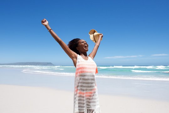 Laughing young woman standing on beach