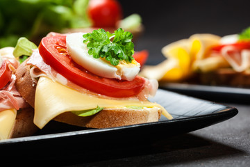 Delicious sandwich with prosciutto ham, cheese, tomato and egg