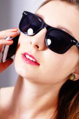 Junge Frau mit Sonnenbrille und Handy