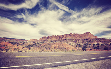 Vintage old film stylized picture of a scenic desert road.