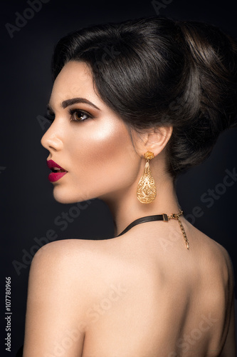 Beautiful woman portrait Young lady posing with gold jewelry