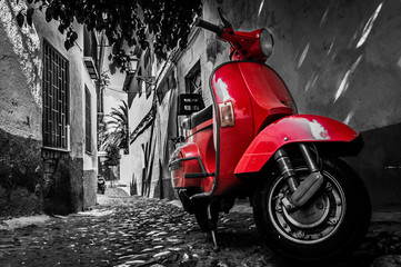 Photo sur Toile Scooter A red vespa scooter parked on a paved street