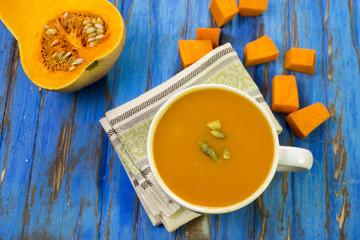 Pumpkin soup puree, blue wooden table, raw pumpkin.