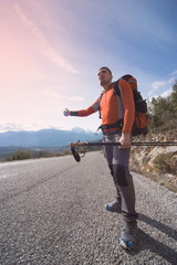 A man with a backpack on the road traveling.
