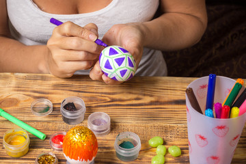 girl paints easter egg with marker, cans, wooden table