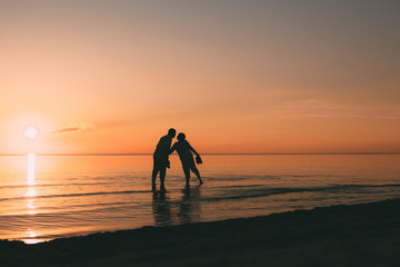Silhouette of adult couple standing in water want to kiss against a sunset.