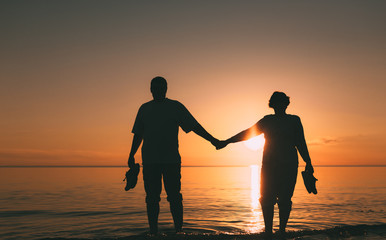 Silhouette of adult couple standing in the sea against a sunset. Evening photo.