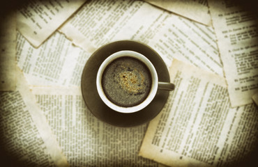 A cup of coffee with coffee beans and a book on a wooden table. Vintage style
