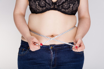 Fototapeta Overweight woman measuring her belly obraz