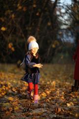 Funny girl running on dry autumn leaves