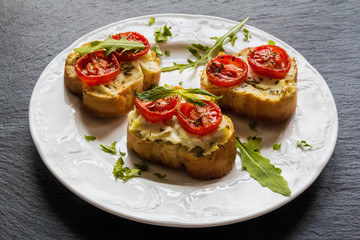 Toasts (Crostini) with ricotta, cherry tomatoes and arugula on black background.