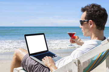 Independent freelancer writing emails on  tropical beach with a