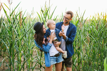 Young hipster family with cute baby in cornfield smiling