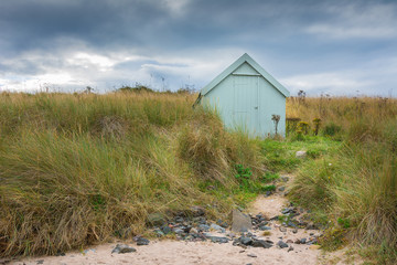 Lonely beach  hut under stormy sky in sand dunes.