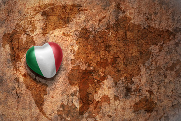 heart with national flag of italy on a vintage world map crack paper background