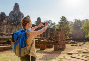 Wall Mural - Young female tourist with smartphone in Bayon temple, Angkor
