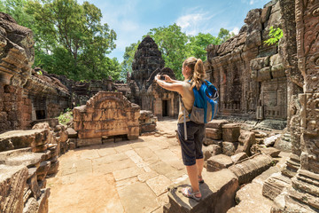 Tourist photographing the bas-relief in Angkor, Cambodia
