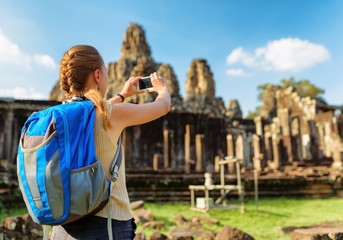 Female tourist with smartphone in Bayon. Angkor Thom, Cambodia