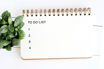 To do list on note book paper on white wood table background